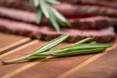 Skivat nötkött för stek för gräsFed saftigt havre som garneras med Rosemary Fresh Herb på naturlig träskärbräda arkivfoto