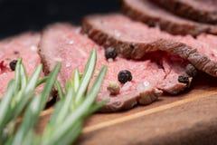 Skivat nötkött för stek för gräsFed saftigt havre som garneras med Rosemary Fresh Herb på naturlig träskärbräda royaltyfri foto