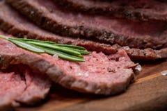 Skivat nötkött för stek för gräsFed saftigt havre som garneras med Rosemary Fresh Herb på naturlig träskärbräda royaltyfri bild