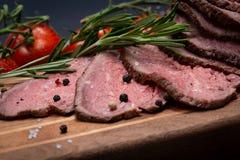 Skivat nötkött för stek för gräsFed saftigt havre som garneras med tomater, nya Rosemary Herb och regnbågepepparkorn royaltyfria foton