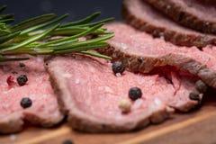 Skivat nötkött för stek för gräsFed saftigt havre som garneras med tomater, nya Rosemary Herb och regnbågepepparkorn arkivbild