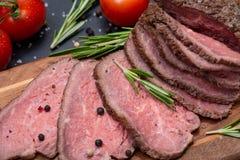 Skivat nötkött för stek för gräsFed saftigt havre som garneras med tomater, nya Rosemary Herb och regnbågepepparkorn royaltyfria bilder