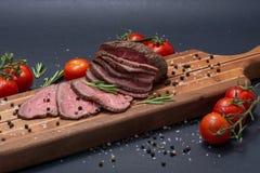 Skivat nötkött för stek för gräsFed saftigt havre som garneras med tomater, nya Rosemary Herb och regnbågepepparkorn royaltyfri fotografi