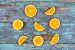Skivat och klippa mogna apelsiner på blå trätappningbakgrund Royaltyfri Foto