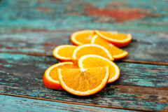 Skivat och klippa mogna apelsiner på blå trätappningbakgrund Arkivbild