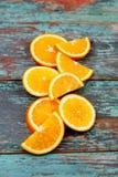 Skivat och klippa mogna apelsiner på blå trätappningbakgrund Royaltyfri Fotografi