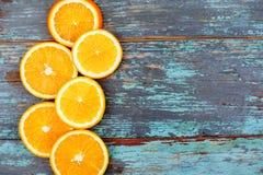 Skivat och klippa mogna apelsiner på blå trätappningbakgrund på vänstra sidan Royaltyfri Fotografi