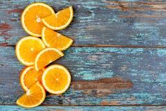 Skivat och klippa mogna apelsiner på blå trätappningbakgrund på vänstra sidan Royaltyfri Foto