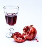 Skivat pomergranate och exponeringsglas av fruktsaft arkivbilder