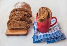Skivat rågbröd på en skärbräda och koppen med mjölkar på taen Arkivbild