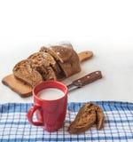 Skivat rågbröd på en skärbräda och koppen med mjölkar på taen Royaltyfri Foto