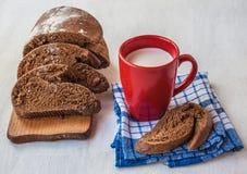 Skivat rågbröd Tabatiere på en skärbräda och röd kopp med Arkivbild