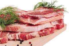 Skivat rått grisköttkött på träbräde Arkivbilder