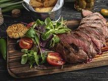 Skivat saftigt sällsynt för biffmedel på brädet med örter, stekte potatisar, kryddor på ett svart yttersidaslut upp royaltyfria foton