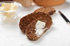 Skivat smakligt bröd med smör på ljus bakgrund royaltyfri fotografi