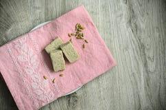 Skivat solroshalva och solrosfrö på ett härligt med den broderade rosa servetten på en träbakgrund royaltyfri foto
