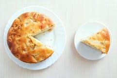 Skivat stycke av kakan på en vit platta Paj på köksbordet arkivbilder