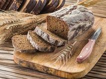 Skivat svart bröd på träplankan royaltyfria bilder