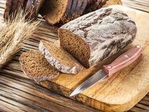 Skivat svart bröd på träplankan royaltyfri foto