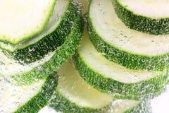 skivat vatten för matlagning zucchinier royaltyfri bild