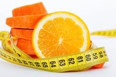 Skivor av apelsinen med skivor av moroten och mätabandet Royaltyfria Foton