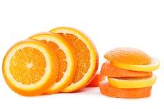 Skivor av apelsinen med skivor av moroten på vit Royaltyfri Foto
