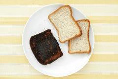 Skivor av bröd med ett stycke av bränt rostat bröd royaltyfri bild