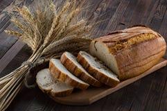 Skivor av bröd på en skärbräda och öron av vete på trät Royaltyfri Foto