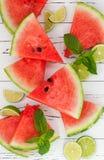 Skivor av den mogna saftiga organiska vattenmelon på den gamla trätabellen som tjänas som med nya limefrukt- och mintkaramellsido arkivfoton