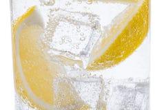 Skivor av den nya saftiga gula citronen med is i klart vatten Royaltyfri Bild