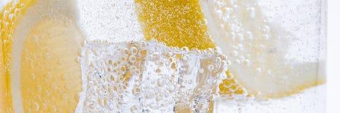 Skivor av den nya saftiga gula citronen med is i klart vatten Fotografering för Bildbyråer