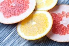 Skivor av den orange och röda grapefrukten Citrusfrukter på textur för tabell för tappninggrå färgfärg Royaltyfri Foto