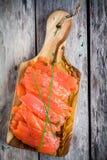 Skivor av den rökte laxen på en träskärbräda med salladslöken Royaltyfri Bild