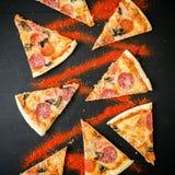 Skivor av italiensk pizza med salami på den mörka tabellen Modell av pizzaskivor Lekmanna- lägenhet, bästa sikt arkivbilder