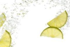 Skivor av limefrukt bevattnar in   arkivbild