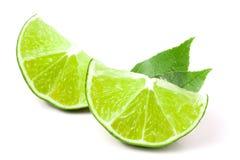 Skivor av limefrukt med sidor som isoleras på vit bakgrund royaltyfri fotografi