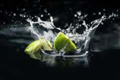 Skivor av limefrukt som faller i vatten royaltyfri fotografi