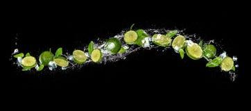 Skivor av limefrukt som faller i vattenfärgstänk på svart bakgrund arkivbild