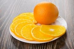 Skivor av mogna apelsiner i den vita maträtten på den mörka tabellen Royaltyfri Foto