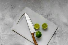 Skivor av ny grön limefrukt på kökljusbrädet arkivbild