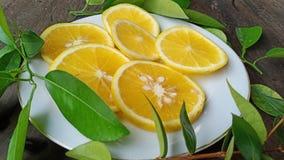 skivor av ny orange frukt på den vita plattan som ska tycks om arkivfoton