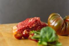 Skivor av ny rå nötköttbiff på träbräde på svart bakgrund med sallad och tomater royaltyfri foto
