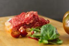 Skivor av ny rå nötköttbiff på träbräde på svart bakgrund med sallad och tomater royaltyfria bilder