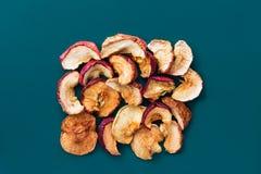 Skivor av olika format och former av den organiska solen torkade frukter torkade äpplen på mörkt - blå turkosbakgrund banta sunt arkivfoto