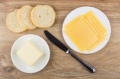 Skivor av ost i plattan, bröd, stycke av smör arkivbild