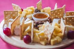 Skivor av ost med druvor, smällare och honung Royaltyfria Foton