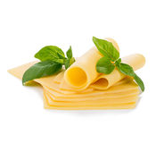 Skivor av ost med ny basilika lämnar närbild isolerad på en vit bakgrund Arkivfoto