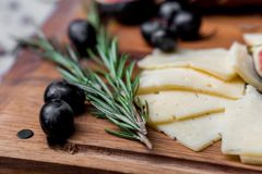 Skivor av ost, oliv och rosmarin ombord arkivfoto