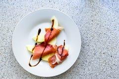 Skivor av Parma skinka och stycken av melon på en platta Royaltyfria Foton