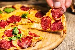 Skivor av pizza med ost och salami i hand på en träplatta royaltyfri fotografi